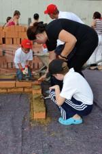 die Nachbarkinder mit ihrer Mutter beim Mauern