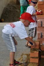 ein süßes Kind beim Mauern auf der Kinderbaustelle