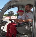 Unser Lagerplatzleiter beim Minibagger fahren mit einem kleinen süßen Mädchen bei der Kinderbaustelle im Zuge der Gemeindesommeraktivitäten 2015